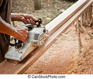 Carpenter working with electric planer in his workshop