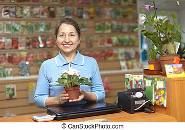 Female saleswoman at store for gardener - Female saleswoman...