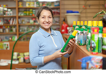mature woman chooses fertilizers at store - Smiling mature...