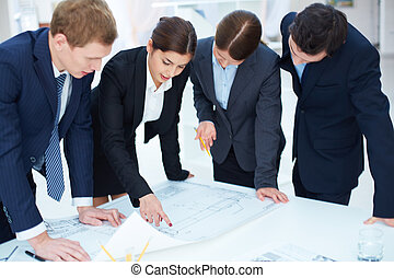 Engineers at work - Team of engineers learning blueprint at...
