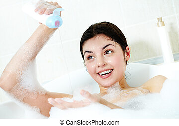 Washing in bath - Image of happy woman going to wash herself...