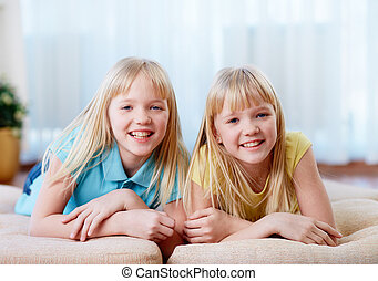 Pretty twins - Portrait of happy twins looking at camera at...