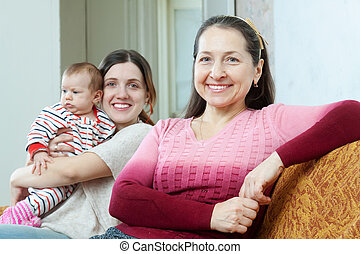 Happy mature woman and adult daughter with baby