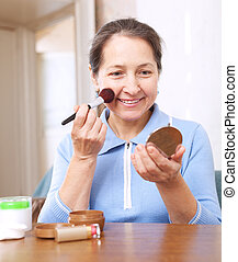 woman putting facepowder on face - woman putting facepowder...