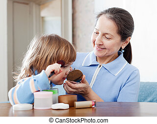 mature woman with granddaughter puts facepowder - Happy...
