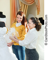 saleswoman helps bride chooses bridal gown at shop of...
