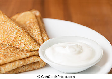 russian crepes with sour cream, on plate