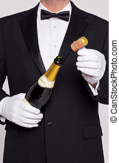 Waiter opening a bottle of champagne holding the cork in his...