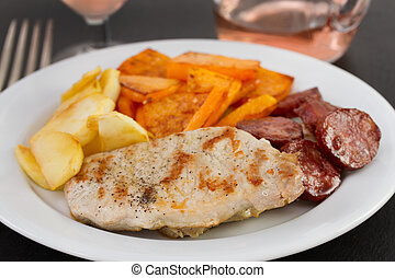 grilled pork with vegetables on the plate