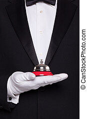 Waiter holding a service bell. - Waiter in black tie and...