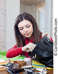 woman can not finding anything in her purse - Young woman...