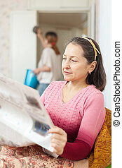 mature woman reads newspaper during adult daughter cleans at...