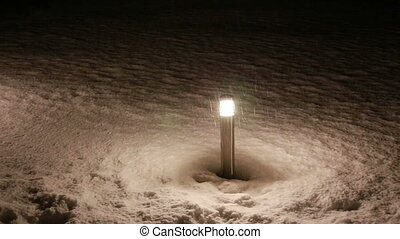 torch in falling snow in the night