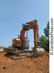 Excavator - Working  with excavator on a heap of red ground