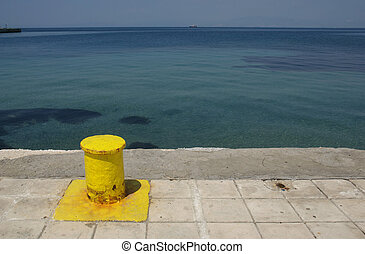 Yellow capstan in port over blue sea