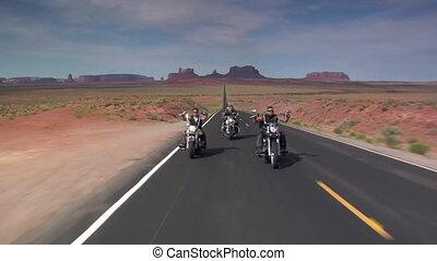 Three bikers on a desert highway, mesas behind