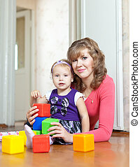mother and baby plays with toys at home