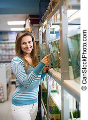 Woman chooses fish in tank at petshop