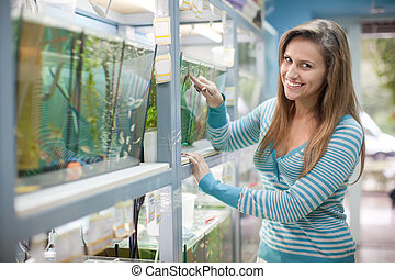 Woman near aquariums in petshop - Woman near aquariums with...