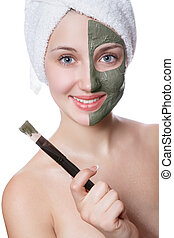 Young woman with facial mask in beauty spa.