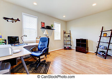 Home office with hardwood floor and simple furniture. - Home...
