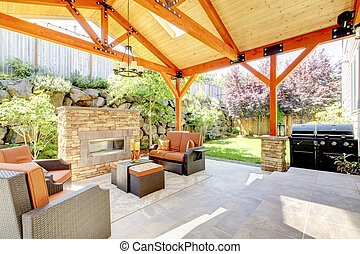 Exterior covered patio with fireplace and furniture Wood...