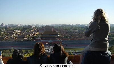 Father carrying daughter to see the Beijing Forbidden...