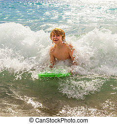 boy has fun at the beach - boy has fun with the surfboard at...