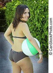 attractive woman in black bikini and beach ball background...