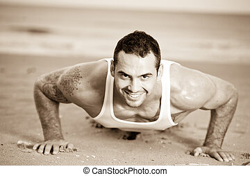 Male exercising on the beach