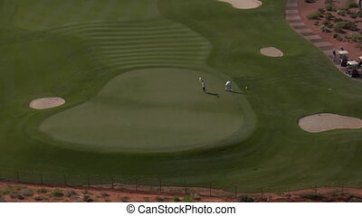 Aerial shot of golfers on the desert course zoom out