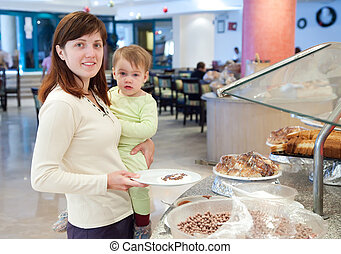 Woman with child  takes  meal in buffet