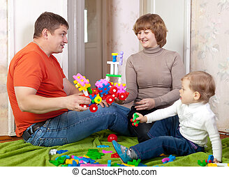 parents and child plays with meccano - Happy parents and...