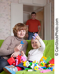 Happy mother and child plays with toys