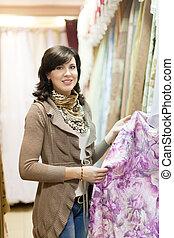 woman chooses draperies - woman chooses draperies at shop...