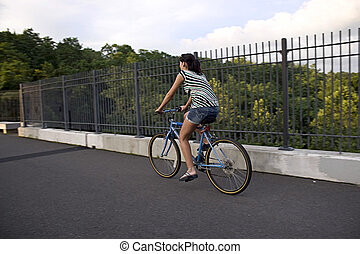 Woman on a Bike - A young woman riding a bicycle across the...