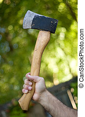 Hatchet - A man holding onto a small hatchet used to chop...