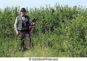hunter with rifle standing in bush