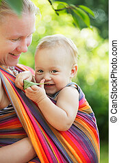 Baby in sling outdoor. Mother is carrying her child and...