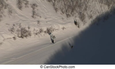 aerial shot of skiers entering shadow