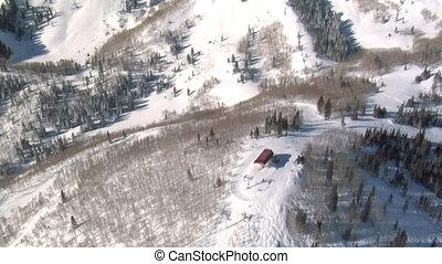 aerial shot of ski resort, lift, and peaks