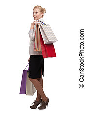 Blonde attractive business woman in a light beige suit holding shopping bags