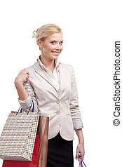 Blonde attractive businesswoman in a light beige suit holding shopping bags
