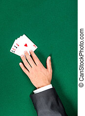 Hand with aces on the poker table