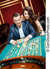 Man accompanied by woman at the roulette table