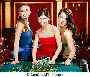 Three women stake playing roulette