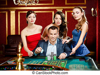 Man surrounded by pretty girls gambles roulette