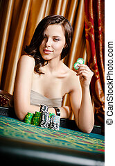 Female gambler at the playing table with chips