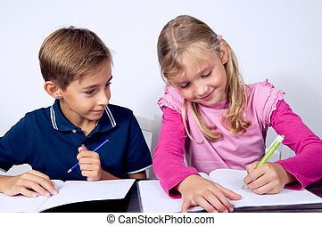 School children writing together - Schoolchildren siting and...