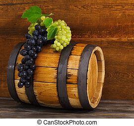 Still life with barrel decorated red and white grapes on...